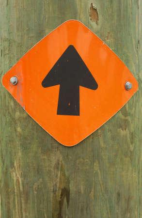 trip hazard sign: One way arrow sign on wood pole.
