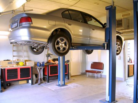 service lift: The lifted car in the auto repairing workshop Stock Photo