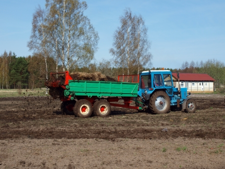 manure: Manure spreading on field by tractor manure spreader Stock Photo
