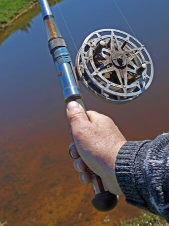 hand line fishing: Hand holding angling rod, view close up Stock Photo