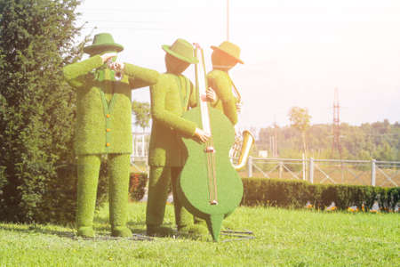 figures playing music carved from the bushes Stock Photo