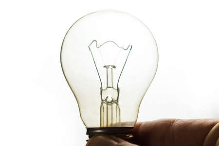 switched off incandescent lamp in hand