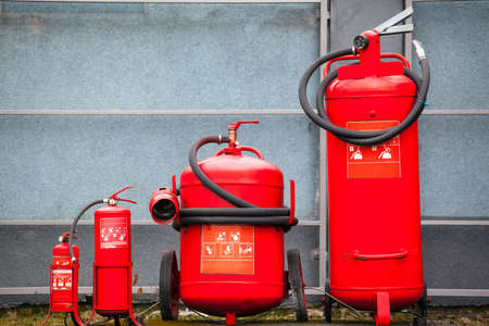 red fire extinguishers of different sizes Stock Photo
