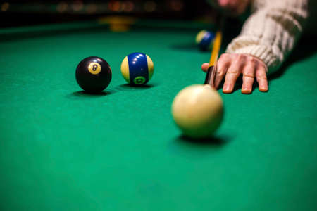 person plays billiards