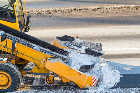 snow-cleaning machinery cleans the street Stock Photo