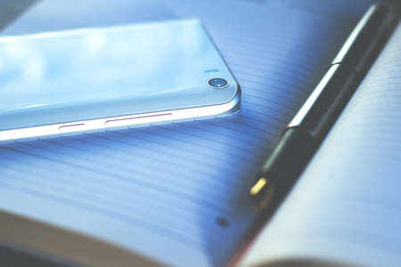 fountain pen and smartphone lie on a notebook, retro toned Standard-Bild