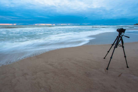 a camera on a tripod on the beach takes off the sea at dusk, long exposure Stockfoto