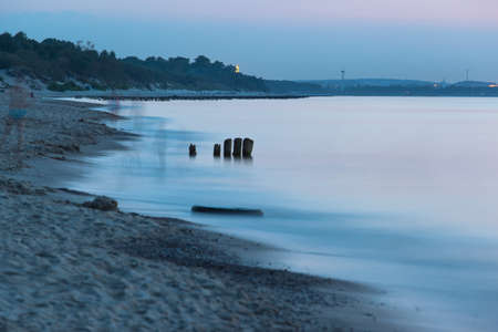 smooth sea surface and coast in blue twilight on long exposure