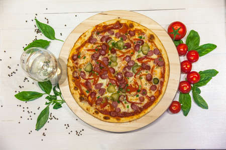 appetizing pizza with small sausages, basil, tomatoes and a glass of white wine on a white table, flat lay