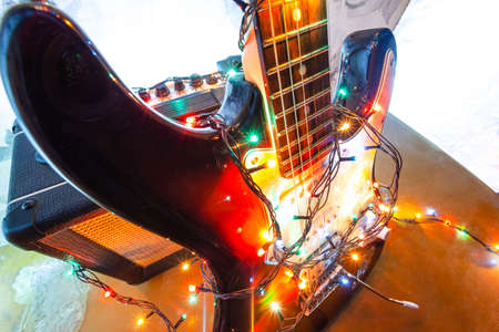 electric guitar and amplifier in bright colors of festive lights of the garland