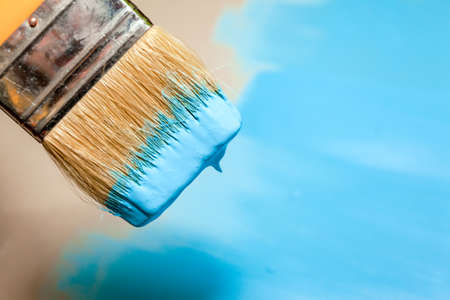 paint brush in blue paint over an unpainted flat surface