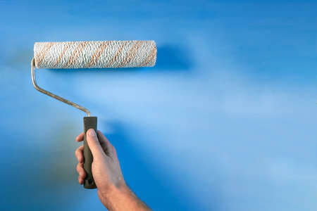 paint roller in male hand on blue background, copyspace