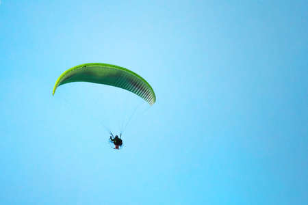 Paraglider flying in the bright blue sky