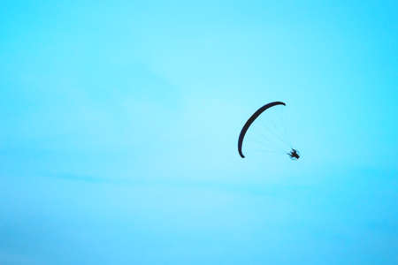 Paraglider silhouette flying in a bright blue sky