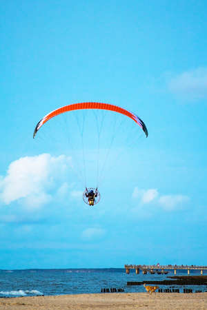 Paraglider flying in the sky over the sea and the beach