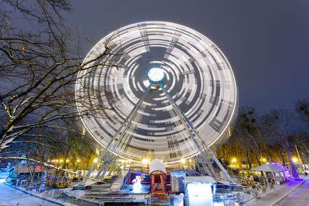bright ferris wheel in night park on long exposure