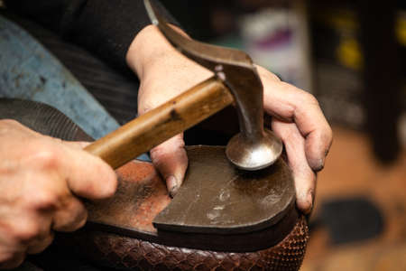 close-up of hands male shoemaker repairing shoes by nailing a heel