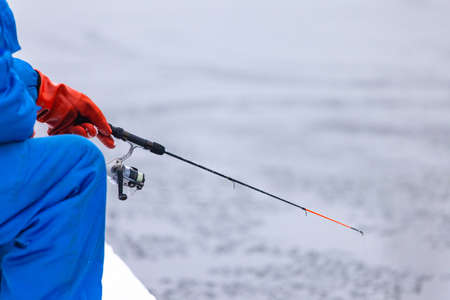 fisherman in the winter engaged in ice fishing