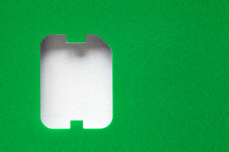 green background with a hole in the shape of a sim card, copy space