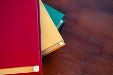 old large books with red, yellow and green covers are on a wooden table, flat lay