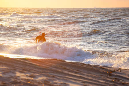 silhouette of a man in a diving suit with a net on the beach collecting amber in the water against the backdrop of a bright orange sunset