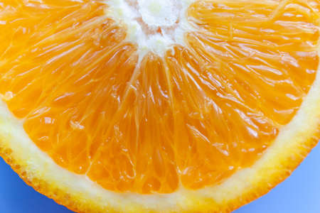 bright slice of juicy orange on a blue background, macro Reklamní fotografie