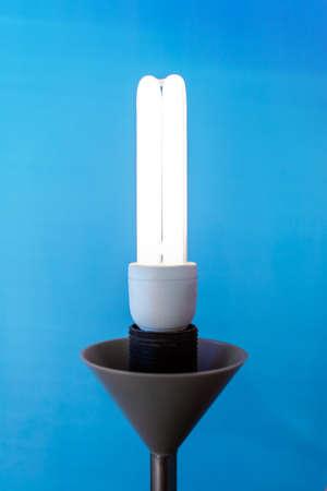 bright energy-saving light bulb in the lamp on a blue background Standard-Bild - 121630227