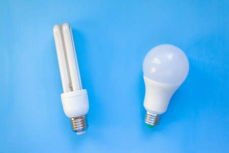 LED and energy-saving light bulbs lie side by side on a blue background