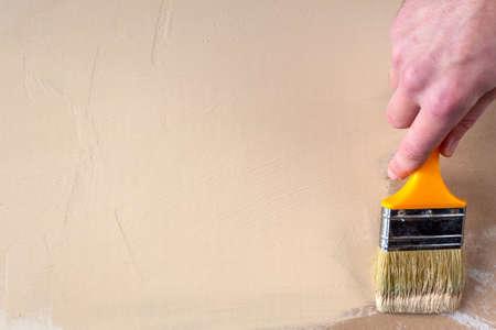 El pintor de la mano del pintor pinta paneles de yeso en color beige, espacio de copia Foto de archivo