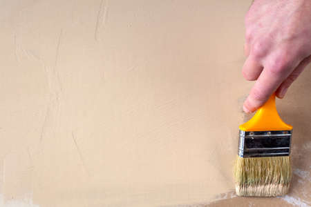 le peintre à la main du peintre peint les cloisons sèches de couleur beige, espace de copie Banque d'images