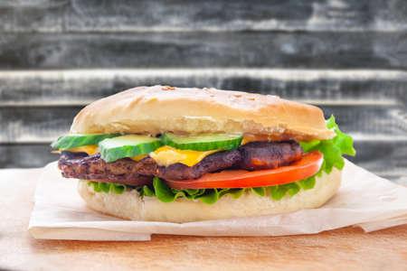 hamburguesa con queso fresco con jugosa chuleta, pepinos, tomate y lechuga Foto de archivo