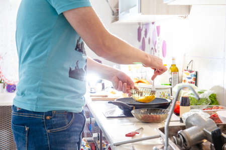 young guy in a brightly lit kitchen preparing food