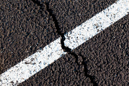 crack on the new asphalt with road markings, top view, background, texture