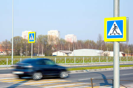 fast moving blurred car at a pedestrian crossing with warning signs