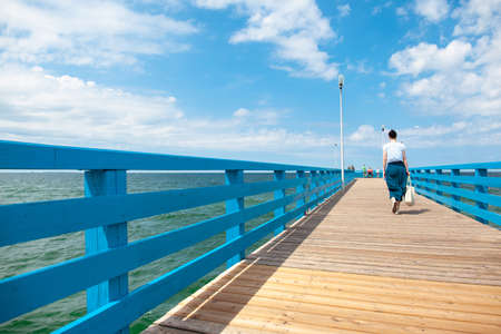girl walks on a sunny summer day along a wooden pier by the sea Stock fotó