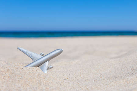 small toy airplane on a sandy beach, concept, copy space