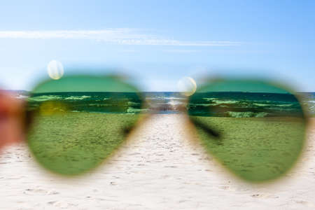 sea and beach on a sunny summer day through green sunglasses