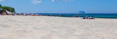 people sunbathe on a public beach on a sunny summer day, panorama