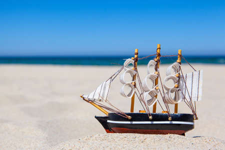 small toy ship on a sandy beach on the background of the sea, concept