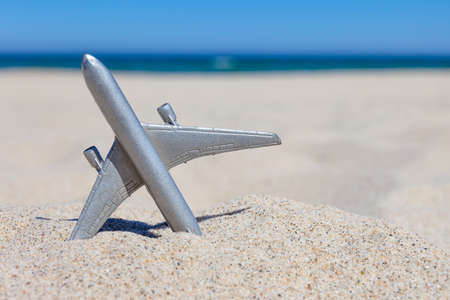 small toy airplane on a sandy beach, concept
