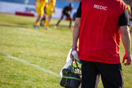medic from the edge of the field watching the game