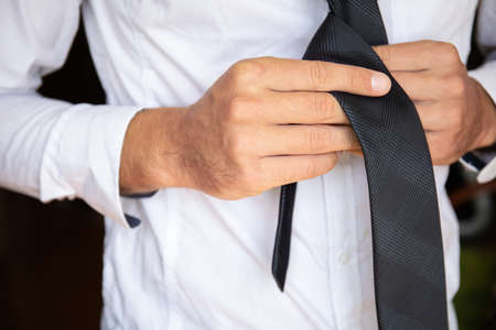 close up of man's hands tying a tie