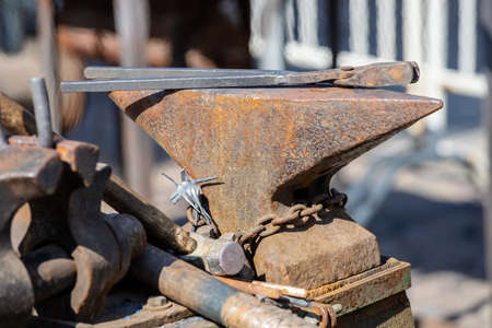 close-up of an old rusty blacksmith anvil with tongs