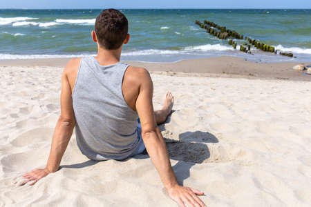 handsome young man sits on the sea beach and looks into the distance Stock fotó - 134718551