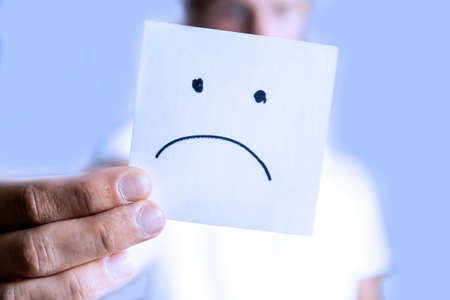 a man holds in his outstretched hand a sheet with a sad smiley