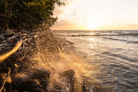 splashing from the waves against the backdrop of a bright orange sunset on the sea