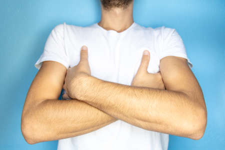 close-up of arms of a man in a white T-shirt crossed on his chest
