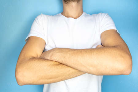 close-up of arms of a man in a white T-shirt crossed on his chest Stock fotó - 134718922
