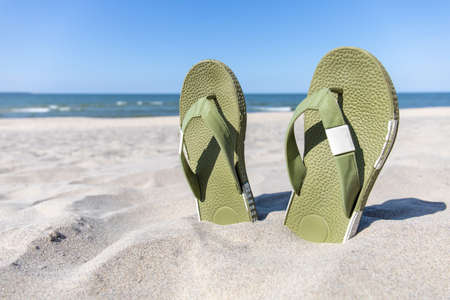male flip flops in the sand against the background of the sea and blue sky