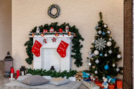 decorated white fireplace with socks and Christmas tree with gifts